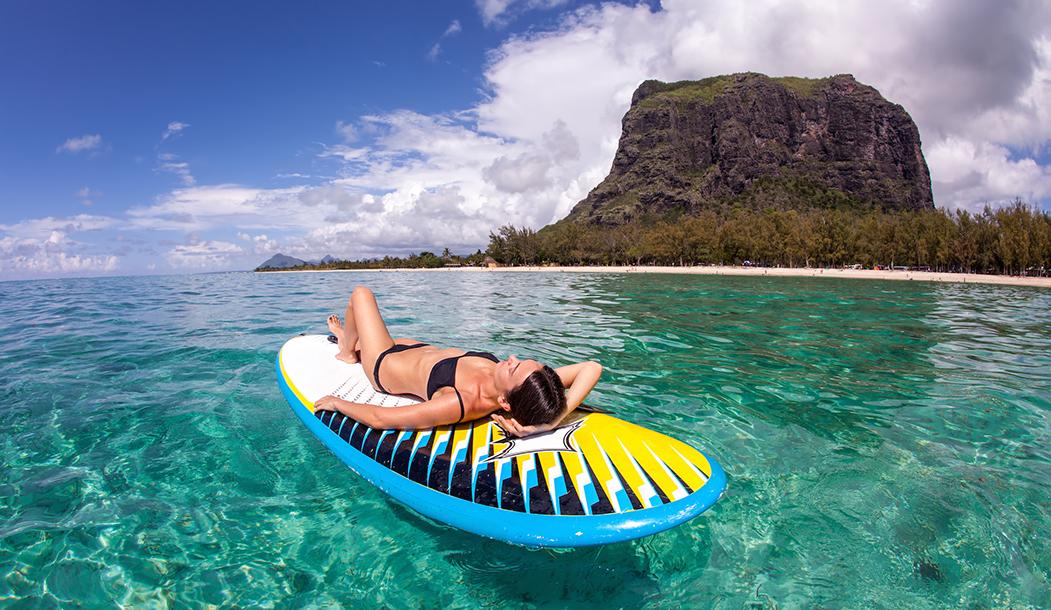 Серферша отдыхает после каталки на фоне гор Маврикия